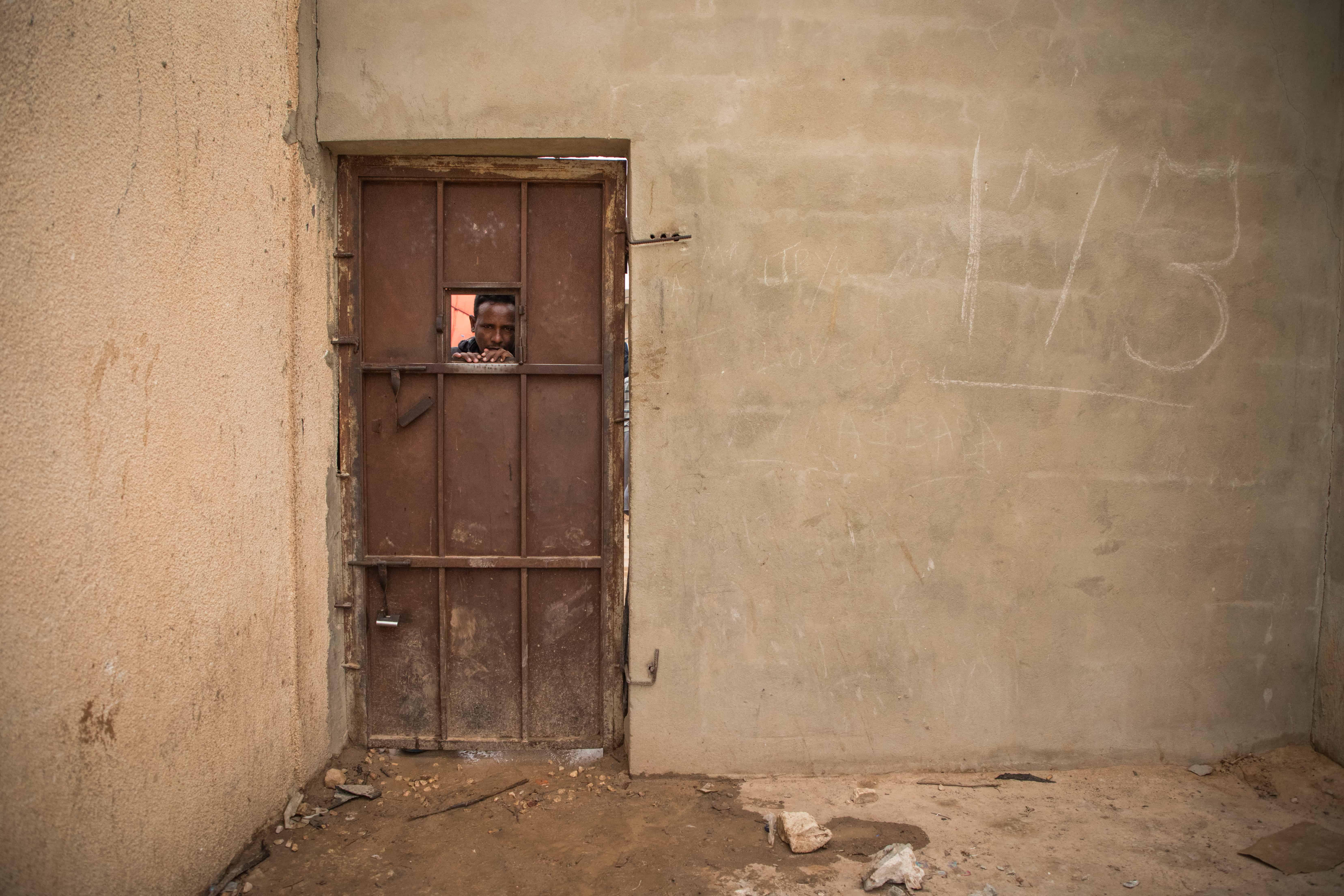 A man peers out through a gap in the gate of the Dahr-El-Jebel detention centre. Libya, October 2019. © AURELIE BAUMEL/MSF